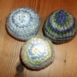 Three hand-knitted easter eggs made with self-striping yarn.